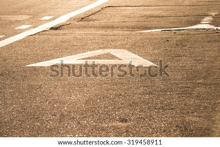 Asphalted traffic lanes against the sun during sunset. Public transport traffic lane. Glowing asphalt with road markings. Close-up. Texture. - stock photo