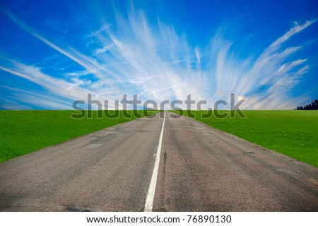 asphaltic road among the green fields - stock photo