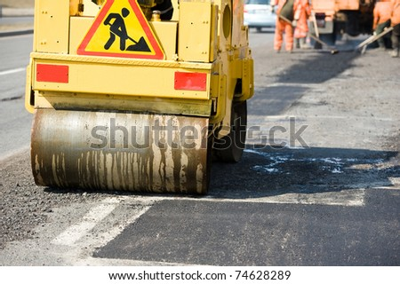 Asphalting paving repairing works with vibrator compactor machine during Road street - stock photo