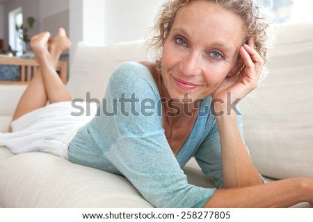 Aspirational close up beauty smiling portrait of an attractive mature healthy woman laying down on a white sofa at home, being thoughtful and relaxing indoors. Home living and well being lifestyle. - stock photo