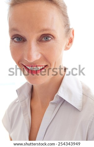 Aspirational close up portrait of a confident and professional mature business woman joyfully smiling to the camera, indoors. Beautiful senior business woman smartly dressed. - stock photo