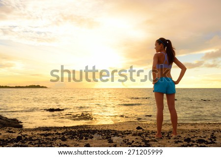 Aspirations - woman looking away with inspiration. Fitness woman after run in sunset on beach looking at ocean feeling peaceful and serene relaxing during summer. Mindfulness concept. - stock photo
