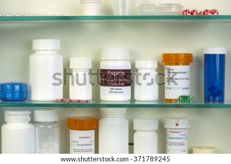 Aspirin bottle in medicine cabinet.  Labels are all fictitious. - stock photo