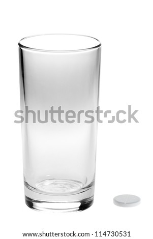 aspirin pills and empty glass isolated on white