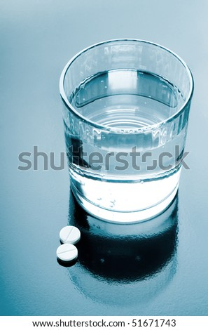 aspirin pills and glass of water on glossy background - stock photo