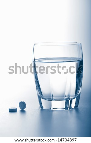 aspirin pills and glass of water toned blue - stock photo
