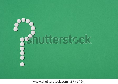 Aspirin tablets in shape of question mark, concepts of health, medical safety, green background to suggest alternative medicine or holistic therapy. - stock photo