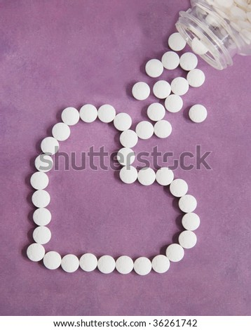aspirin therapy for your heart - aspirin in the shape of a heart on purple textured paper - stock photo