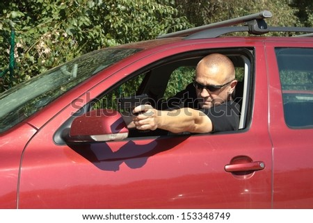 assassin shooting from a moving car, aggressive driver - stock photo