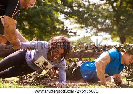 Assault course competitor helping others crawl under nets - stock photo