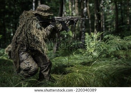 Assault of polish camouflaged soldier with assault rifle in forest - stock photo