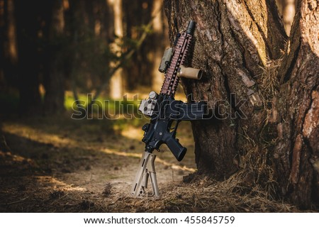 assault rifle leaning on a tree in the forest - stock photo