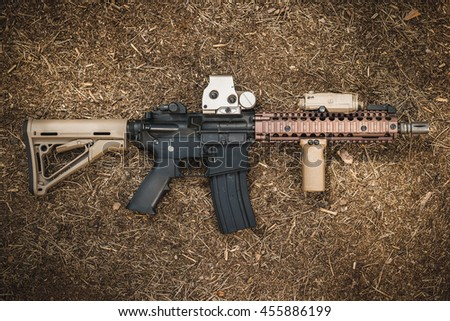 assault rifle on the forest ground - stock photo