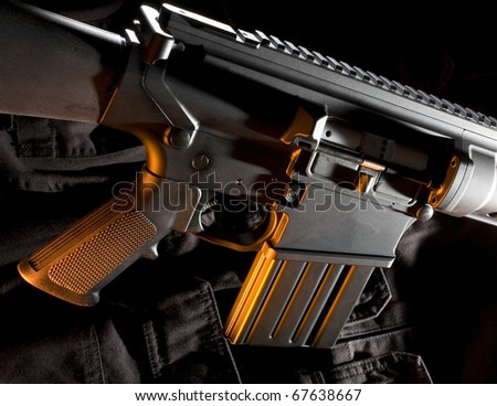 assault rifle that is black with an orange color from the side - stock photo