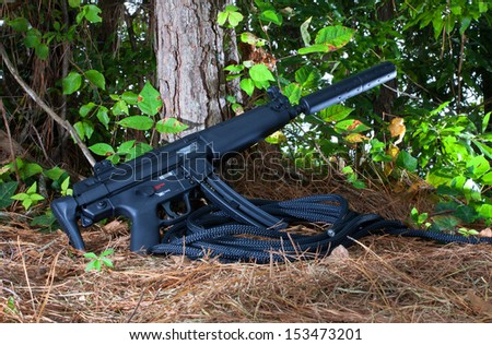 Assault rifle with a silencer attached in the woods - stock photo