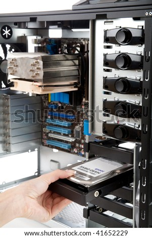 Assembling a high performance personal computer, Mounting a Hard Drive in to a new Hi-end PC, shallow depth of field, focus on hand and Hard Drive - stock photo
