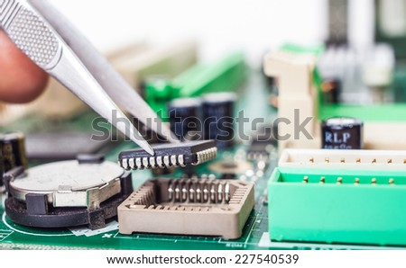 assembling computer parts with tweezers on the motherboard - stock photo