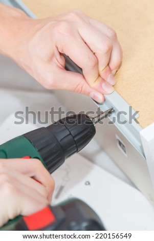 Assembling  Furniture with a screwdriver - stock photo