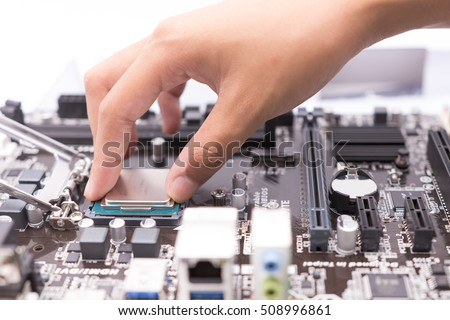 Assembling high performance personal computer, inserting CPU, processor into the motherboard socket, opened PC case in background, shallow depth of field, focus on CPU