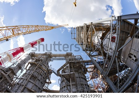 Assembly and installation of large vertical reactor at a refinery with heavy-duty crawler crane - stock photo