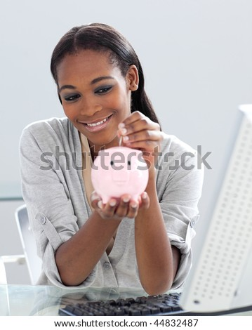 Assertive Afro-american businesswoman saving money in a piggybank at her desk - stock photo