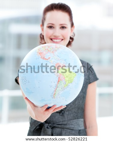 Assertive businesswoman holding a terrestrial globe in the office - stock photo