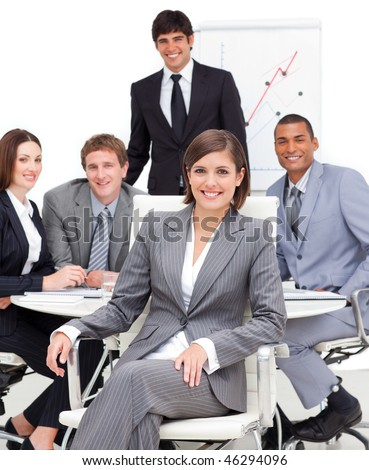 Assertive female executive sitting in front of her team in a meeting - stock photo