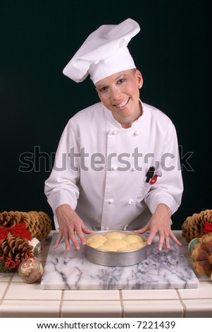Assertive posed uniformed female Pastry Chef showing dinner rolls for the oven at her baking station amid Christmas ornamentation.