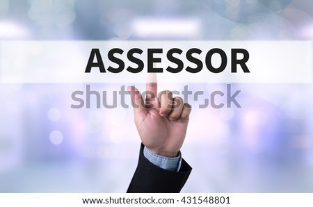 ASSESSOR Business man with hand pressing a button on blurred abstract background - stock photo