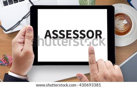 ASSESSOR Business team hands at work with financial reports and a laptop, on the tablet pc screen held by businessman hands - online, top view - stock photo