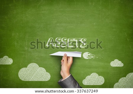 Assets concept on green blackboard with businessman hand holding paper plane - stock photo