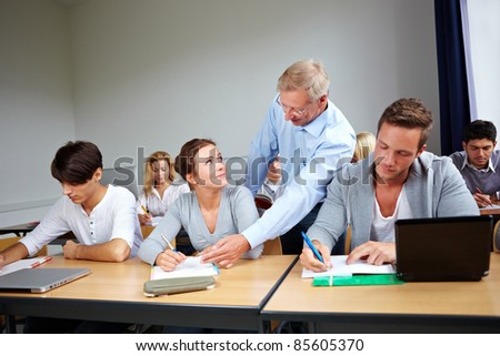 Assistance of students at university with a teacher - stock photo