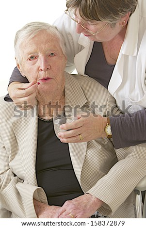 assistance to disabled elderly to take medicine - stock photo