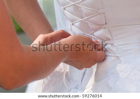 Assistant girl lacing up brides white corset. Horizontal shot - stock photo