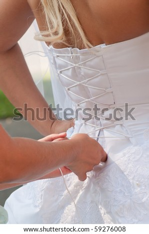 Assistant girl tightening brides white corset. Vertical shot - stock photo