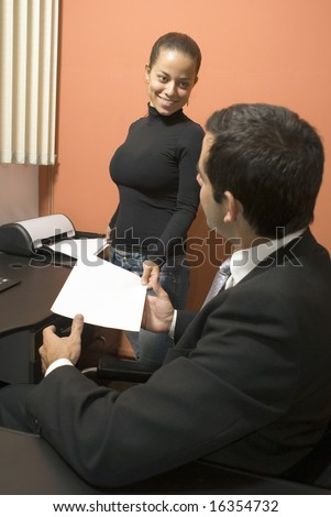 Assistant handing a businessman a piece of paper from the printer. Vertically framed shot. - stock photo
