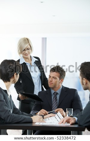 Assistant handing report to executive at meeting in office.
