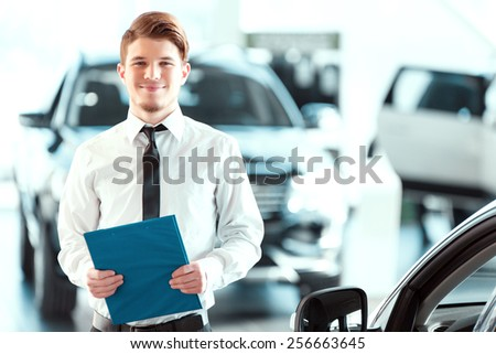 Assistant in vehicle search. Portrait of a handsome young car sales man in formalwear holding a clipboard and looking at camera in a car dealership  - stock photo