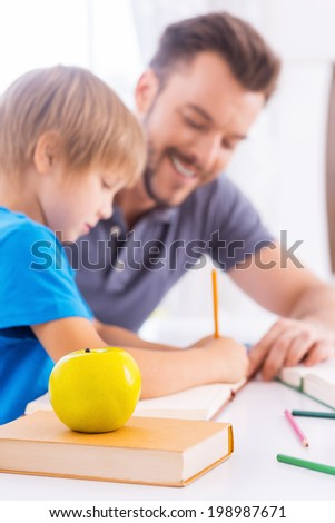 Assisting son with schoolwork. Side view of cheerful young father helping his son with homework and smiling while sitting at the table together with green apple laying on the foreground - stock photo