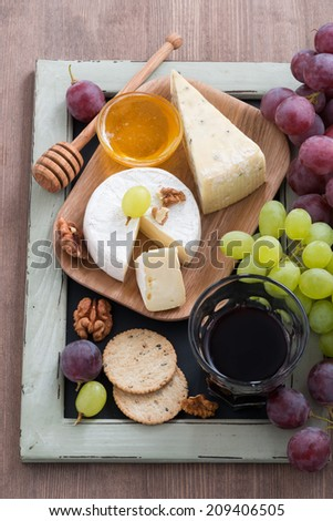 Assorted appetizers to wine - cheeses, fresh grapes, crackers and honey, top view, vertical - stock photo