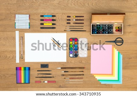 Assorted array of arts, crafts, drawing and design items, such as pens, rulers, markers, felt tip pens, fountain pens brushes, watercolor, and various sheets of paper on a wooden surface - stock photo