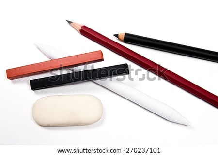 Assorted Art Tools. Pencils, eraser, stamp, chalk of sanguine and charcoal. Isolated over white background.