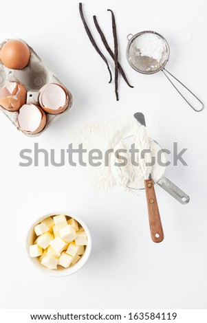 Assorted baking ingredients and tools: eggshells, vanilla pods, flour in measuring cup, spatula, butter and vintage sifter with icing sugar. Taken on a white background,  from above. - stock photo