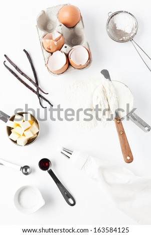 Assorted baking ingredients and tools: eggshells, vanilla pods, flour in measuring cup, spatula, measuring spoon with vanilla extract, butter, sea salt, piping bag and vintage sifter with icing sugar. - stock photo