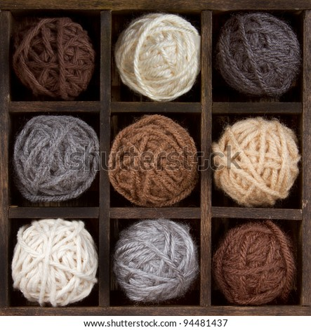 Assorted balls of natural colored yarn in a printers box - stock photo