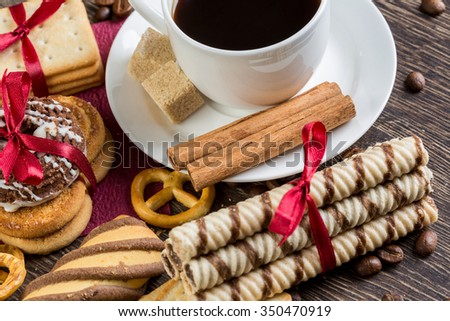 Assorted biscuits and sweets with a cup of coffee on table - stock photo