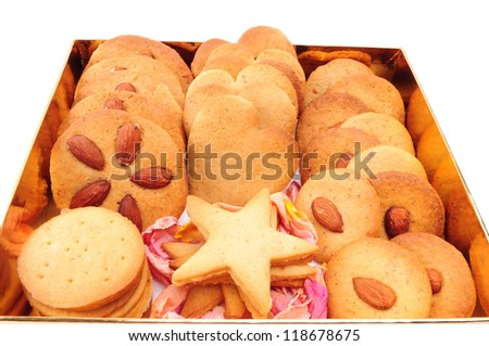 Assorted biscuits in a gold box, isolated on white background. Christmas baking. Gift packaging.