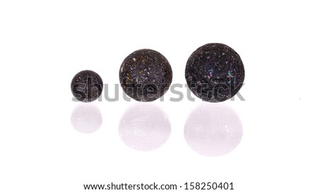 Assorted black glass marbles arranged over a white background, very old - stock photo