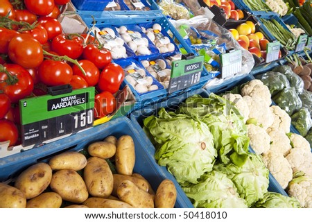 Assorted boxes and crates with fresh fruit and vegetables on display at a greengrocery - stock photo