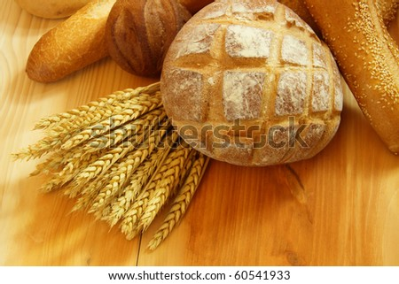 Assorted bread on wooden table with raw wheat - stock photo